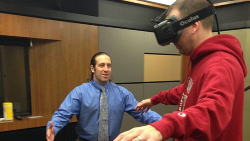 Lab director Jeremy Bailenson leads a student through a VR exercise