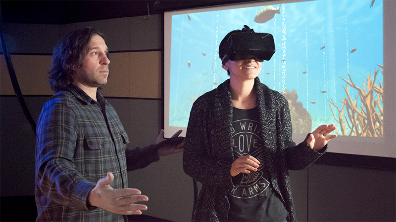 Jeremy Bailenson helps a user experience Coral World in VR